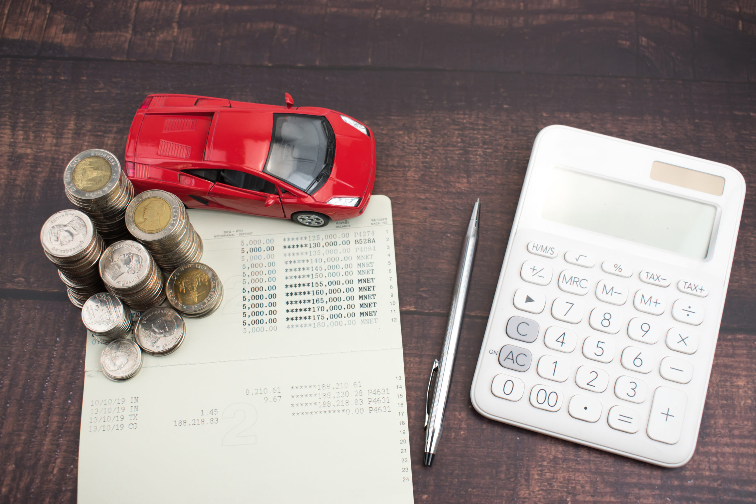 Pile of coins, black ballpoint pen, calculator and red car on paper form Increased spending for car purchases. Finance, buy a car.